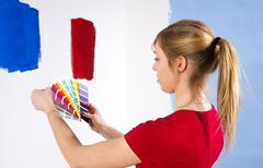Young woman holding colour cards in front of a wall with colour samples Stock Photos