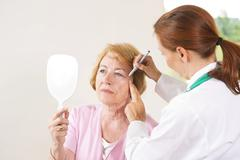 woman being marked by her doctor before cosmetic surgery - stock photo