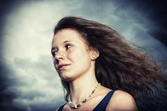 girl, 14 years, with long hair in front of a gloomy cloudy sky, portrait - stock photo