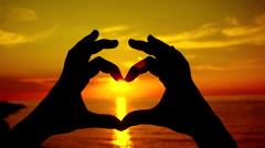 SLOW MOTION: Sunset sun shining through heart shaped hands - stock footage