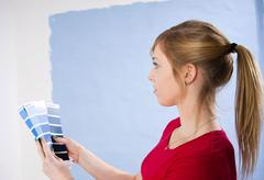 young woman holding colour cards in front of a wall - stock photo