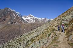 hikers ascending hintere eggenspitz mountain in ulten valley above the weissb - stock photo