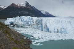 glacial ice from the perito moreno glacier calving into the lake of lago arge - stock photo