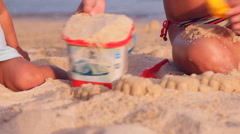 Mother and child make figures out of the sand on the beach Stock Footage