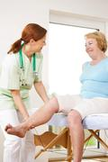 orthopedic surgeon examining the knee of a patient - stock photo