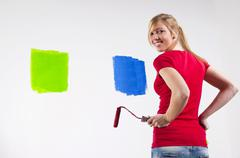 Young woman holding two paint rollers in front of a wall with paint samples Stock Photos