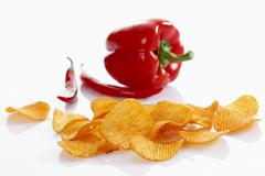 paprika potato chips in front of a capsicum and chili peppers - stock photo