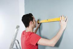 young man using a spirit level - stock photo