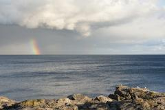 rainbow, dark clouds, rocky coastline on great head, acadia national park, ma - stock photo
