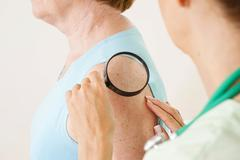 dermatologist examining a patient with a magnifying glass - stock photo