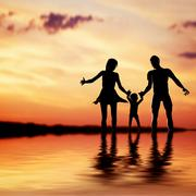 happy family walking together hand in hand at sunset. mother, father and a li - stock illustration