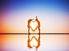 A happy couple in love making a heart shape with their bodies at sunset with  Stock Illustration