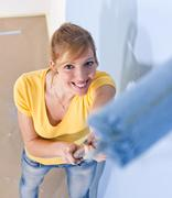 young woman painting a wall - stock photo