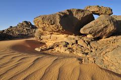 sandstone rock formation and sand dunes, adrar tekemberet, immidir, algeria,  - stock photo
