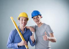 Two young tradesmen holding a spirit level Stock Photos