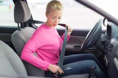 Beautiful woman fastening seat belt. - stock photo
