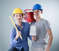 two young tradesmen holding a tool box, a trowel and a spirit level - stock photo