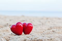 Two red hearts on the beach symbolizing love, valentine's day, romantic coupl Stock Photos