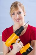young woman holding a drill - stock photo