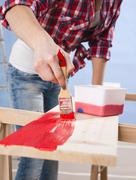 young woman painting a board with a brush - stock photo