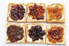 Stock Photo of six slices of toast with various jams, rhubarb jam, apricot jam, strawberry j