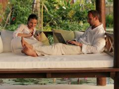 Young couple with laptop and smartphone on gazebo bed in garden NTSC Stock Footage