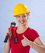Young woman wearing a yellow safety helmet and holding a bolt cutter in her h Stock Photos