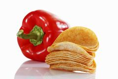 Oval paprika potato chips, stacking chips, stacked beside a capsicum Stock Photos