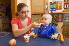 Mother, 28 years, feeding baby, 1 year Stock Photos
