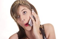 Surprised young woman holding a mobile phone to her ear Stock Photos