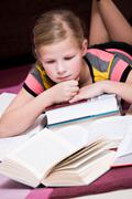 Girl, 11, lying between books Stock Photos