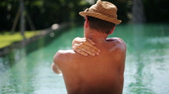 Young man applying suns block lotion on  his arms at edge of swimming pool  HD Stock Footage