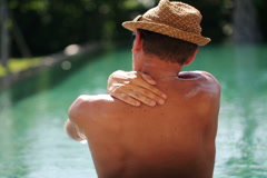 Young man applying suns block lotion on  his arms at edge of swimming pool  NTSC Stock Footage