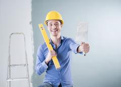 Young tradesman holding a spirit level and a trowel Stock Photos