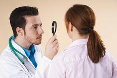 Dermatologist examining a suspicious skin area of a patient with a magnifying Stock Photos