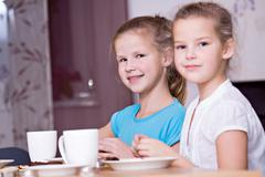 Two girls, 11 and 8, sitting at a laid table Stock Photos