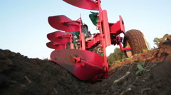 Tractor plowing the black earth plow field at sunset Stock Footage