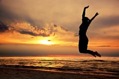 Happy woman jumping on the beach at sunset. success, energy, wellbeing concep Stock Photos