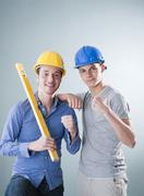 two young tradesmen holding a spirit level - stock photo