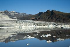 Stock Photo of glacier tongue coloured black from ashes, reflection, joekulsárlón glacial