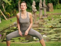 Young woman doing squats in the garden NTSC Stock Footage