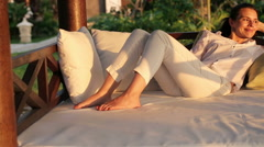 Beautiful woman relaxing on gazebo bed in garden HD Stock Footage
