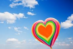 Colorful heart shaped lollipop on sky background. love, fun, valentine's day Stock Photos