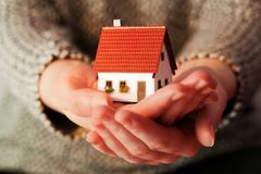 Woman holding a small new house in her hands. real estate, mortgage, housing  Stock Photos