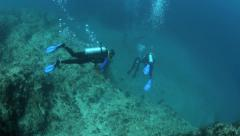 Scuba divers descending down coral reef wall to ocean floor Stock Footage