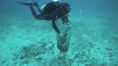 Scuba diver collecting underwater trash - stock footage
