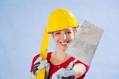 young woman wearing a yellow safety helmet holding a spirit level and trowel  - stock photo
