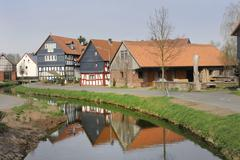 half-timbered houses being reflected in the water of the treisbach creek, amo - stock photo