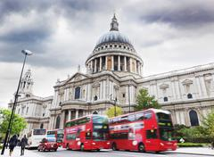 St paul's cathedral in london, the uk. red buses in motion, cloudy sky Stock Photos