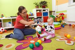 mother, 28 years, playing with baby, 1 year - stock photo
